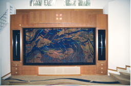 Built-in speakers beneath art. The art is made of braids and is hiding a projection screen. Cabinet by www.rngcabinetshop.com